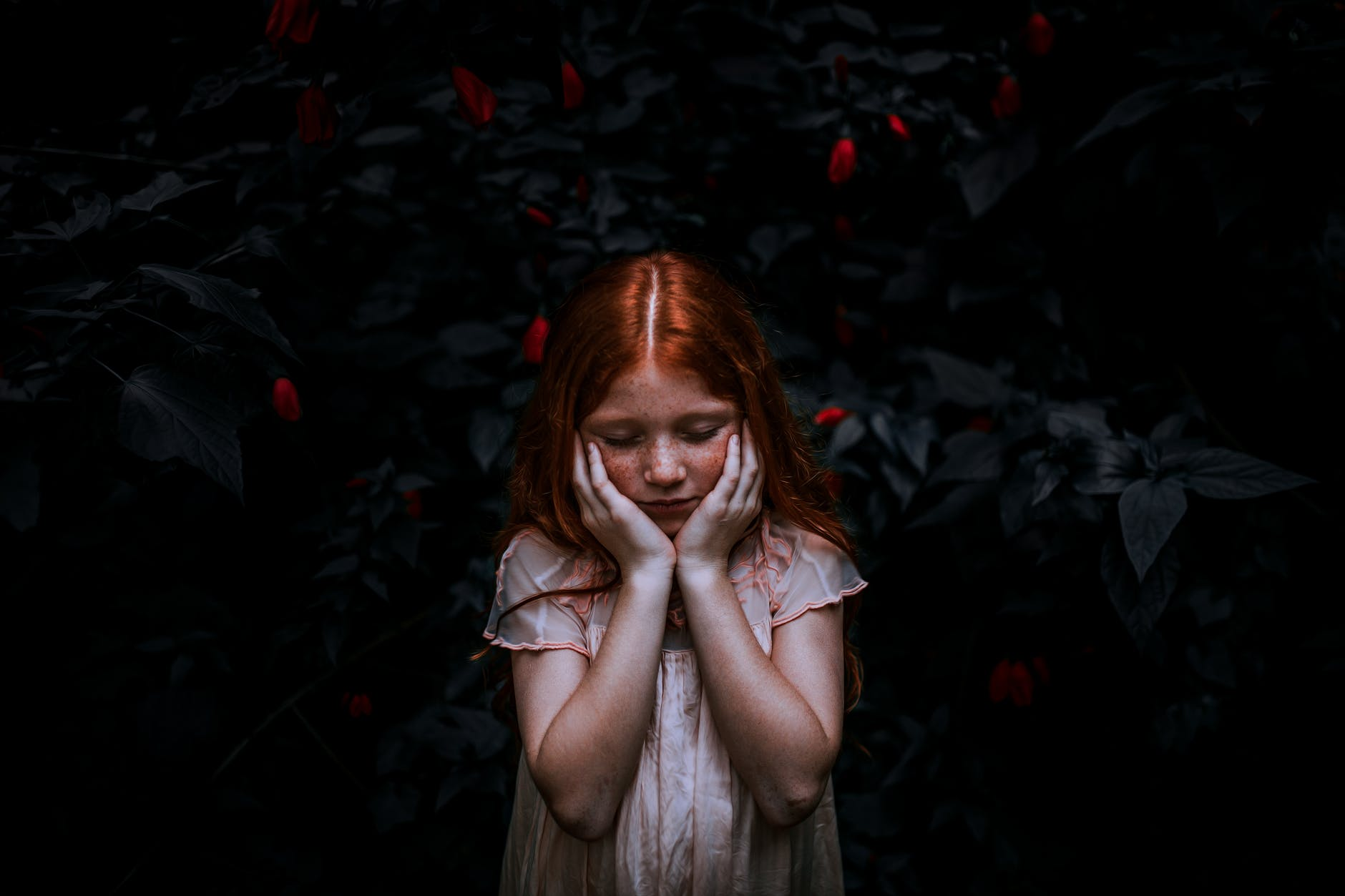 red haired girl standing near plant